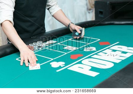 Croupier At The Poker Table In The Casino. Chips And Cards On The Table