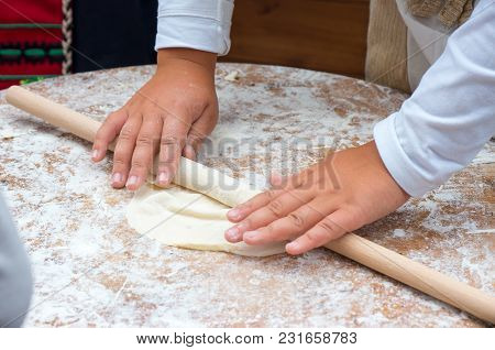 Girl Rolling Dough With Rolling Pin. Preparation Of The Dough On The Wooden Table With Flour.