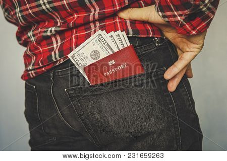 Red Unidentified Passport In A Pocket Of Jeans. Pocket Money For Personal Expenses During Trips And