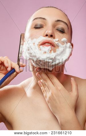 Beautiful Woman With Fake Mustache, Beard And Open Razor On Pink Background Has Shave
