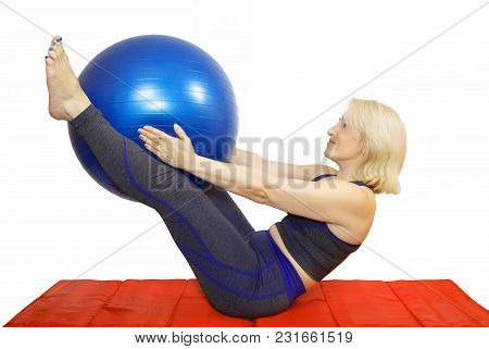 A Middle-aged Woman Performs A Physical Exercise From Pilates,compresses Kicking The Ball The Fitbal