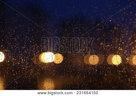 Rain Bokeh In A Window. Nigth City. Rain Drops On Glass.