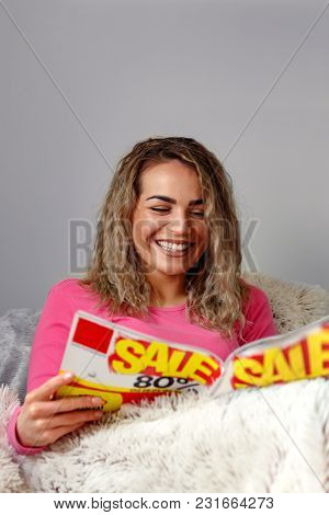 Beautiful Happy Beautiful Woman Reading A Magazine In Bed At Home