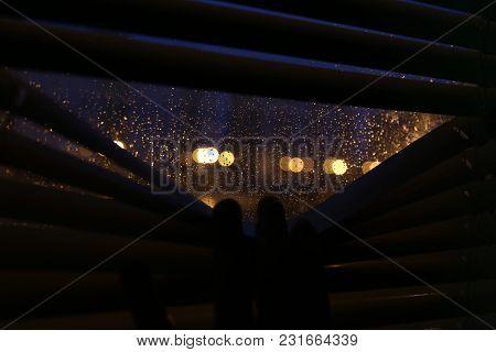 Rain Bokeh In A Window. Nigth City. Rain Drops On Glass. Look Through Blinds
