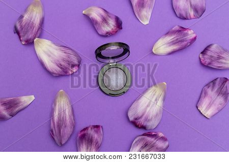 Purple Eyeshadow And Petals On A Purple Background. Flat Lay
