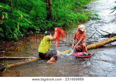 Kanchanaburi, Thailand - September 16, 2011: Rural Housewifes Sitting On Lying Down Tree Trunk To Wa