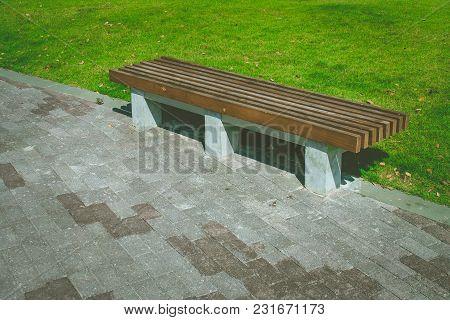 Wooden Long Bench Setting On Concrete Walkway Beside Green Grass Meadow Field At Public Park. (selec