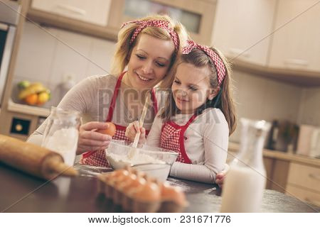 Young Mother In The Kitchen Baking Dough With Her Daughter, Breaking An Egg While Daughter Is Stirin