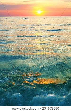 Dramatic Colorful Sea Sunset With Sun Setting On Water Lonely Boat On Horison And Dark Waves On Fore