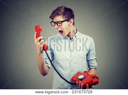 Young Man Screaming On The Red Phone
