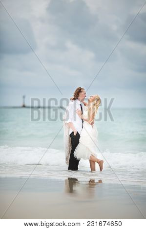 Bride In Wedding Dress And Groom Hugging At The Sea. Couple Love On Deserted Beach. Marriage Registr