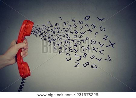 Hand Holding Telephone Handset With Alphabet Letters Coming Out. Too Many Words During Conversation