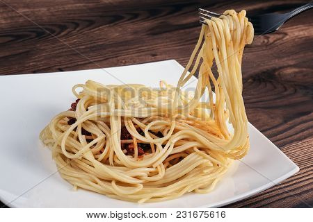 Fork Pull The Spaghetti. Someone Is Going To Eat A Delicious Pasta With A Fork. The Paste Lies On A