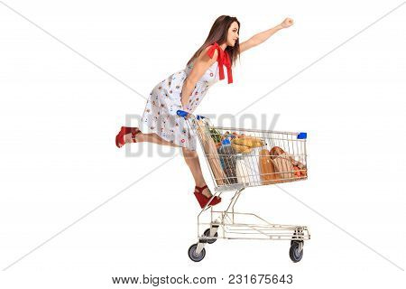 Woman With Shopping Cart Full With Products Isolated Over White Background. A Young Woman Rides For