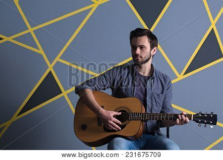 Man With A Guitar On A Gray Wall Background