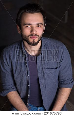 Young Handsome Man With A Beard On A Dark Background