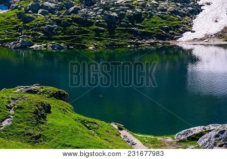 Belea Lake In Fagarasan Mountains Of Romania. Beautiful Nature Summer Scenery With Grassy Slopes, Ro
