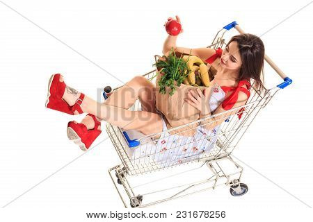 High Angle View Of Girl Smiling At Camera While Holding Grocery Bags And Sitting In Shopping Trolley