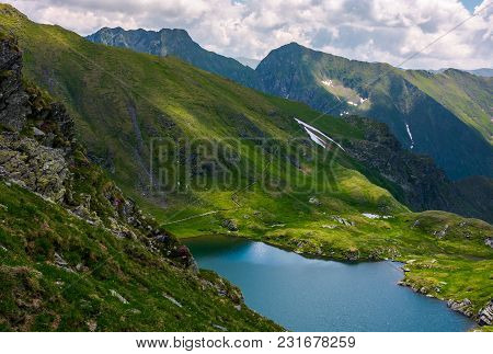 Lake Capra In Fagarasan Mountains Of Romania. Beautiful Summer Scenery On A Cloudy Day. Popular Tour