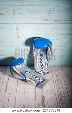 Silver And Blue Boxing Gloves On Blue And White Cracked Wooden Background, Empty Space