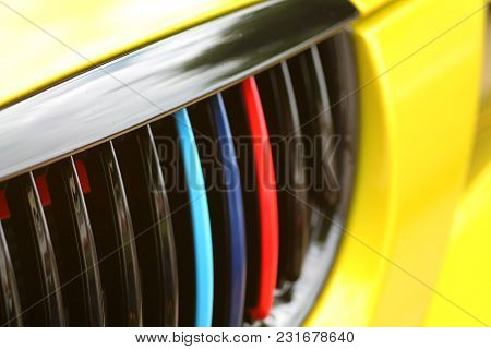Colorful Front Grille Of A Car. Background, Concept Of Expensive Auto Detailing.  Automotive Paint.