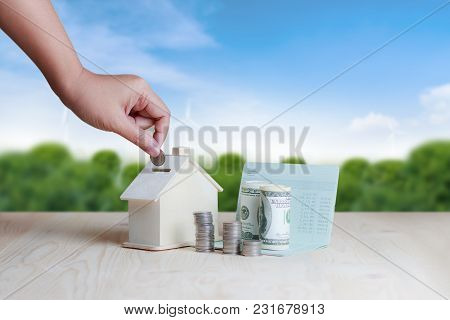Woman Hand Putting The Coin In To Wooden House Piggy Bank Financial Metaphor Saving Money For Buy Ho