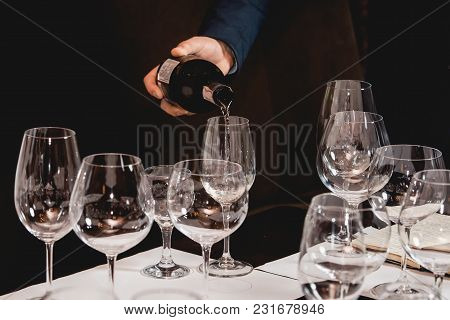 Served Table At Wine Tasting. Sommelier Pouring Red Wine From A Bottle Into Glass
