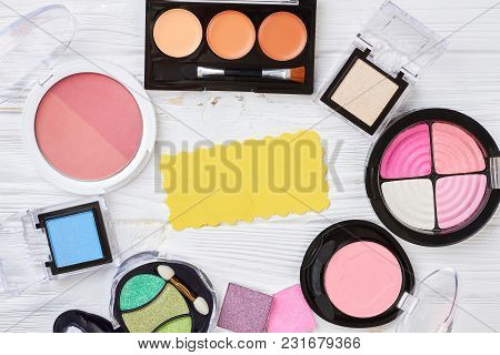 Blank Paper And Set Of Cosmetics. Collection Of Eyeshadows And Blushers On White Wooden Background.