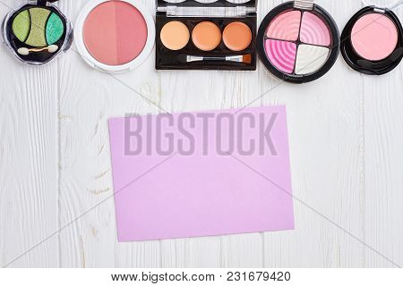 Set Of Eyeshadows And Blushers, Top View. Blank Paper Sheet On White Wooden Background. Eye Make Up