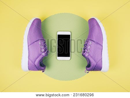 Flat Lay Shot Of Sneakers And Smartphone On Yellow Background With Copy Space For Your Text.