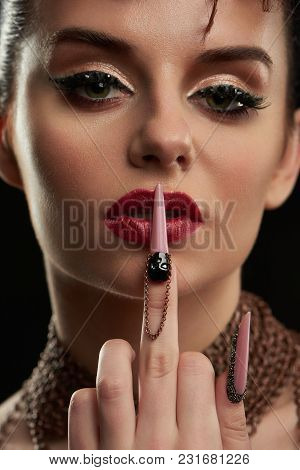 Close Up Of Confident Girl Warrior With Bright Makeup, Touching Red Lips By Finger With Long Nail. F