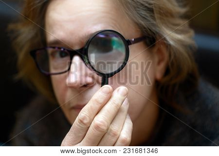 An Elderly Woman Looks With One Eye Through A Magnifying Glass. Read Like A Book.