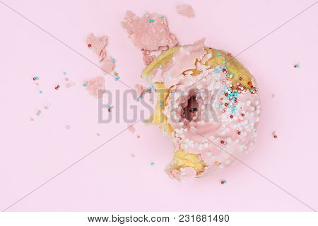 Part Of A Bitten Strawberry Donut With A Fragile Icing, Colorful Powder On A Pink Background. A Big