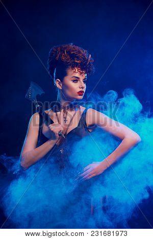 Portrait Of Dangerous Beatiful Girl Keeping Sharp Metallic Axe With Thorns. Confident Model Wears Bl
