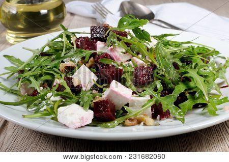 Salad From Roasted Beets, Arugula, Cheese Feta, And Walnuts. Horizontal Shot. Foreground Close-up.