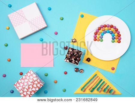 Colorful Still Life With Sweets And Present On Blue Background. Top View, Creative Flat Lay With Cop