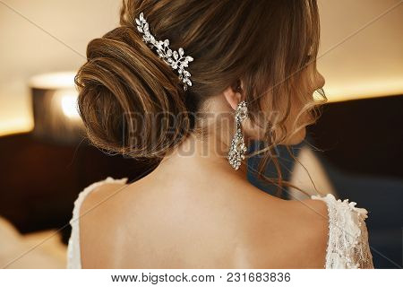 Wedding Hairstyle - Fashionable Brown-haired Young Woman, In A Lace Dress And With Earrings.