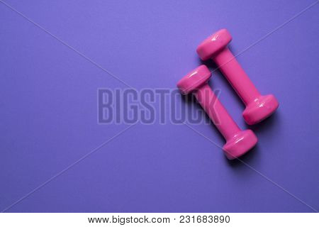 Two Pink Dumbbell On Purple Background, Sport And Healthy Concept