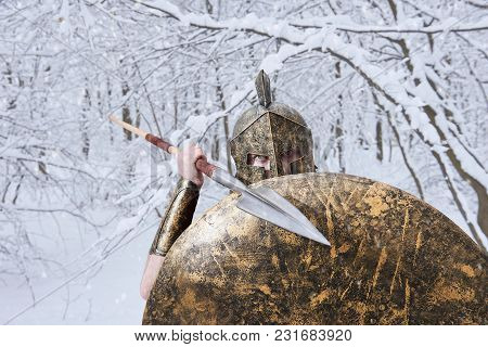 Spartan Attacks Someone With Sharp Metallic Spear In Winter Forest. He Wers Traditional Spartan Armo