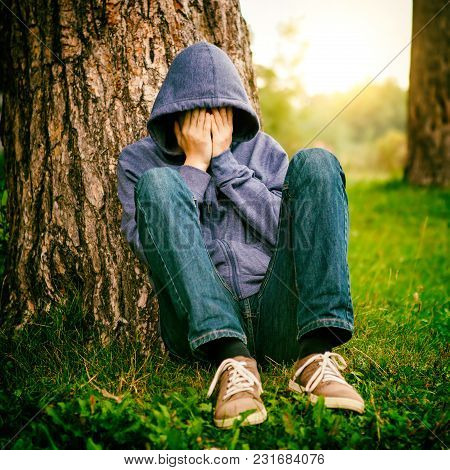 Toned Photo Of Sad Young Man Sit Under The Tree In The Park