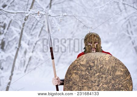 Spartan Keeping Spear And Shield In Snowy Forest. He Is Wearing Red Long Cape Is Stealing Through Wi