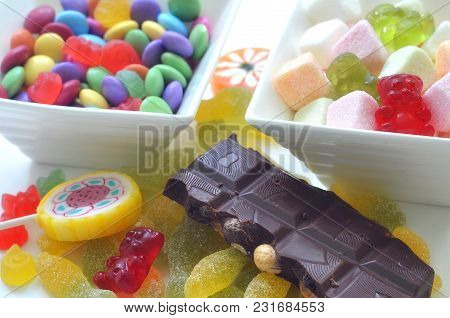 Two Ceramic Bowls Of Colored Smarties, Sour Candies, Chocolate, Lollipop And Gummy Bears On White Ba
