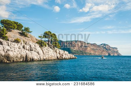 Boat Passing By White Cliffs Of Massif Des Calanques Covered With Pine Trees In Cassis Near Marseill