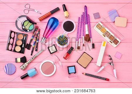 Flat Lay Decorative Cosmetics, Top View. Makeup Tools And Accessories On Pink Wooden Background. Wom