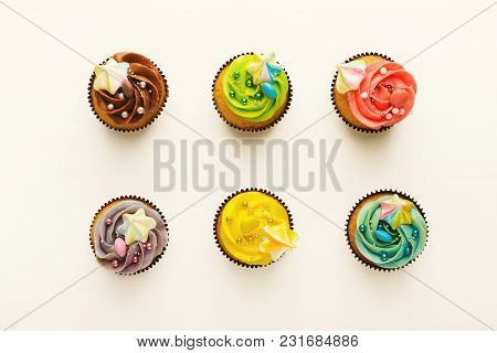 Top View On Set Of Vanilla Cupcakes With Colorful Buttercream Tops Isolated On White Background. Tas