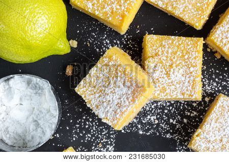 Lemon Bars Close Up On Black Background - Top View Photo Of Baked Small Lemon Squares With Whole Lem