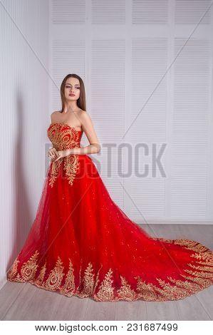 Elegant Sensual Young Woman In Beautiful Red Dress Posing Indoor