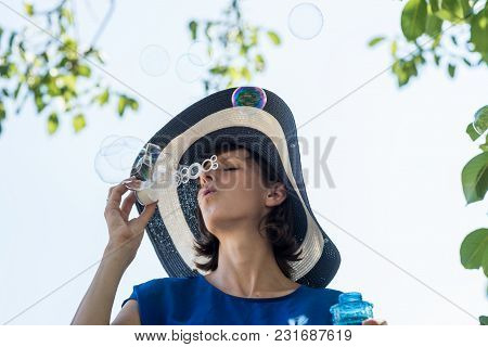 Attractive Woman In A Wide Brimmed Sunhat Blowing Bubbles Under Tree On A Hot Sunny Summer Day.