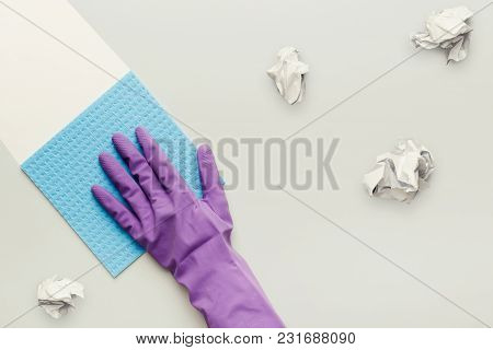 Hand In Protective Rubber Glove With Blue Rag And Crumpled Papers. Woman Washing White Surface With