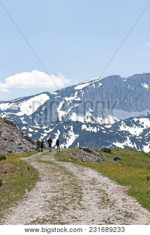 Four Mountaineers Walking On The Mountain Trail To The Mountain Maglic, Highest Mountain In Bosnia A